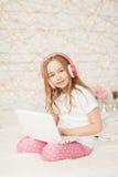 Musica e tecnologia Ritratto della ragazza in pigiami con il computer portatile bianco e le cuffie rosa senza fili su fondo Fotografia Stock Libera da Diritti