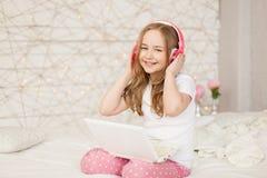 Musica e tecnologia Ritratto della ragazza in pigiami con il computer portatile bianco e le cuffie rosa senza fili su fondo Immagine Stock Libera da Diritti
