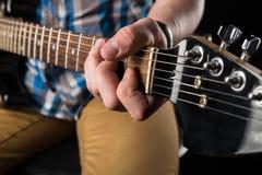 Musica ed arte Chitarra elettrica nelle mani di un chitarrista, su un fondo isolato il nero Gioco della chitarra Struttura orizzo Immagine Stock