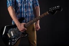Musica ed arte Il chitarrista tiene una chitarra elettrica in sua mano destra, su un fondo isolato il nero Gioco della chitarra h immagini stock