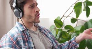 Musica favorita d'ascolto dell'uomo sulle cuffie mentre cantando e giocando Air guitar stock footage