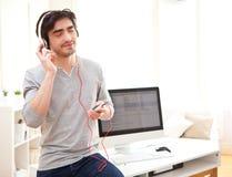 Musica listenning del giovane uomo rilassato all'ufficio Fotografia Stock Libera da Diritti