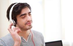 Musica listenning del giovane uomo rilassato all'ufficio Fotografie Stock Libere da Diritti