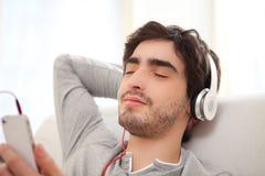 Musica listenning del giovane uomo rilassato nel sofà Fotografia Stock