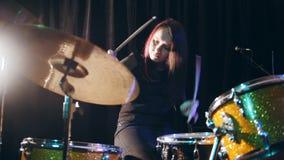 Musica rock teenager - il batterista precipitantesi appassionato della percussione della ragazza esegue la musica riparte stock footage