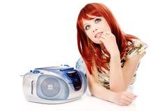 Musica situantesi e d'ascolto della ragazza graziosa Immagini Stock Libere da Diritti