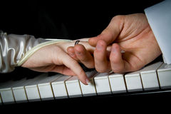 Musical. Newlyweds holding each other hands over piano keyboard royalty free stock photos