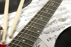Musical abstraction. Electric guitar, drumsticks, mediator and records on the notes Stock Photo