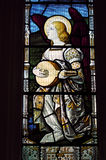Musical angel. A Victorian stained glass window depicting an angel playing the lute. An historic window, over 100 years old, on public display at St Mary stock photos