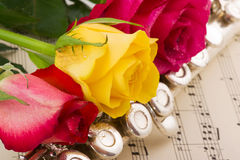 Musical arrangement. With rose and silver flute Stock Photography
