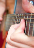 Musical arrangements. Singer hands on the acoustics guitar playing a rock  song Stock Image