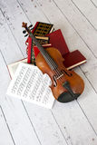 Musical art. Picture of a violin on a stack of books Stock Photos