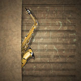 Musical background sax on old sheet music notation Stock Photo