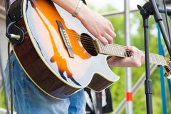 Musical band perfom on an open air festival. Guitarist man playing music sunburst color acoustic guitar. Musical band perfom on an open air festival. Guitarist royalty free stock images