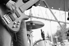 Musical band perfom on an open air festival. Bass guitarist man playing close, drums blurred. Black and white toned photo Royalty Free Stock Images