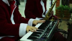 Musical band in Santa Claus suits playing merry melody to create Xmas atmosphere. Stock footage stock footage