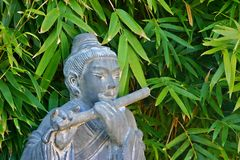 Musical Chinese statue. Chinese statue of person playing woodwind instrument with bamboo plants in background Royalty Free Stock Photography