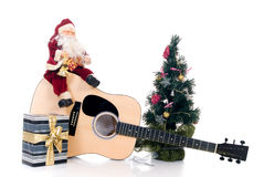Musical  Christmas. Christmastime with Santa Claus sitting on guitar with present, isolated on white background Stock Image