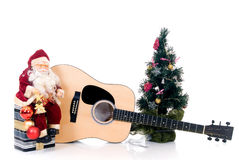 Musical  Christmas. Christmas tree with Santa Claus sitting on present in front of guitar, isolated on white background Stock Photo