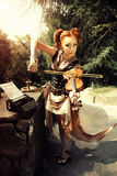 Musical concept. Attractivel young woman in rock style clothes p. Laying on violin outdoors Royalty Free Stock Images