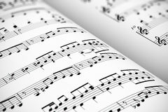 Sheet music. Musical concept background: macro view of white score sheet music with notes with selective focus effect Stock Image