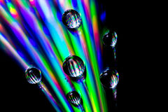 Musical drops. A cd with drops on it, shined on with a led light giving a very colourful effect Stock Photography