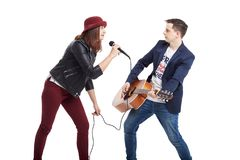 A musical duo of a young couple, a singer in a red hat with a mi. Crophone and a handsome guy in a blue jacket with an acoustic guitar. Isolated on white Stock Photos