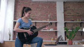 Musical education, happy beautiful guitarist girl learning play stringed musical instrument uses laptop computer with. Online video lesson and enjoy music at stock video footage