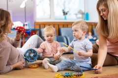 Musical education for preschoolers. Parents play musical toys with their children royalty free stock photography