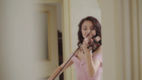 Musical, emotionally craft by exultant female violinist at camera in light room. 4K stock footage