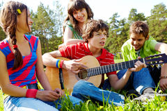 Musical entertainment. Portrait of handsome lad playing the guitar surrounded by his friends Royalty Free Stock Photo