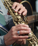 Musical fingers. Close-up of hands and fingers of a jazz musician on keys of a brass instrument stock photography