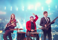 Musical group in suits, performing on the rooftop. Retro style, night cityscape on background. Guitarists and drummer, rock band Stock Photos