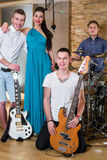 Musical group of three guys and one girl in Recording Studio Royalty Free Stock Photography