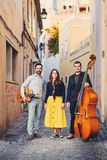 A musical group of three people on an old European street. The band consists of two men and one girl. Men with a double bass and a. Guitar. Unconventional stock photo