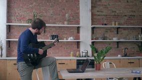 Musical hobby, joyful bearded guitarist guy learning play stringed musical instrument uses laptop computer with online. Video training and enjoy music at home stock video footage