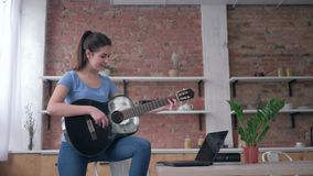 Musical hobby, smiling instrumentalist girl learning play stringed musical instrument uses laptop computer with online. Video training and enjoy music at home stock video footage