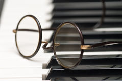 Musical inspiration. John Lennon-style glasses, over the keys of a piano Stock Images