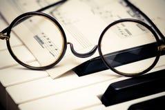 Musical inspiration. John Lennon-style glasses, over the keys of a piano Stock Photo