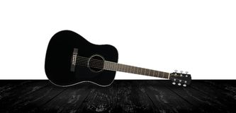 Musical instrument - Black acoustic guitar brick and white backg. Musical instrument - Black acoustic guitar on a white background and black wooden floor Royalty Free Stock Photography