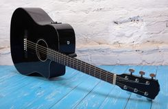 Musical instrument - Black cutaway acoustic guitar brick backgro. Musical instrument - Black cutaway acoustic guitar on a brick background and blue wooden floor stock photography
