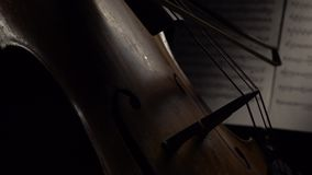 Cello in the dark bow bow on the strings behind the notes. Close up. Side view. Musical instrument cello in the dark bow bow on the strings behind the notes stock video