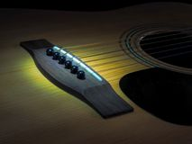 Musical instrument classical acoustic guitar of light color with steel pins and silver strings on a dark background.  stock photos