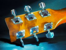Musical instrument classical acoustic guitar of light color with steel pins and silver strings on a dark background.  stock image