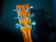 Musical instrument classical acoustic guitar of light color with steel pins and silver strings on a dark background.  royalty free stock images