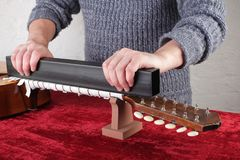 Guitar repair and service - Worker grinds guitar neck frets. Musical instrument guitar repair and service - Worker grinds guitar neck frets Royalty Free Stock Photo