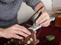 Guitar repair and service - Worker polishing guitar neck frets d. Musical instrument guitar repair and service - Worker polishing guitar neck frets dremel and Royalty Free Stock Photography
