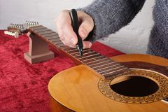 Guitar repair and service - Worker preparation of frets for grin. Musical instrument guitar repair and service - Worker preparation of frets for grinding Royalty Free Stock Image