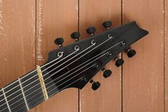 Musical instrument - headstock neck tuning peg 8 string guitar. Musical instrument - headstock peghead neck tuning peg 8 string guitar on a wood background royalty free stock images