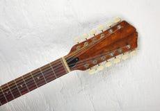 Musical instrument - headstock twelve-string acoustic guitar. Musical instrument - headstock peghead twelve-string vintage acoustic guitar on a white brick wall Stock Photo